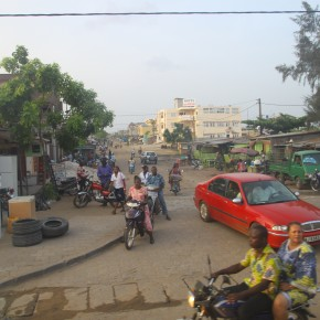 2011-04-07 Benin, Cotonou - street scene with motos and merchandise on the street for sale