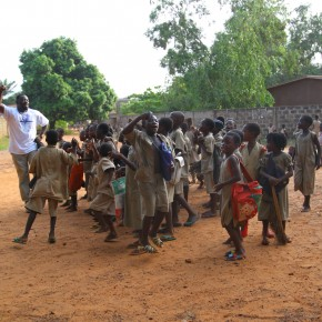 2011-04-07 Benin, Ouidah - Our Trans Africa guide, Noah came upon this group of children on their way from school and joined them in a lively set of songs. They wear khaki uniforms.