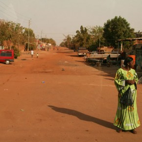 2009-01-17 Burkina Faso, Ouagadougou, dressed up woman walking in the dusty street
