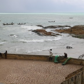 2011-04-10 Ghana, Tokaradi, Cape Coast Castle - a fort built by Portuguese for the Slave trade; fishermen repairing nets on one of the ramparts; boats in the distance coming in from fishing