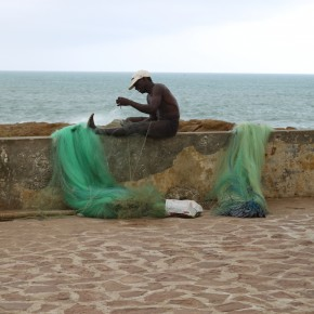 2011-04-10 Ghana, Tokaradi, Cape Coast Castle - fisherman repairing net on the fort rampart