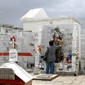 2020-12-26 Chile, Punta Arenas - A woman makes a prayer and leaves an offering at the shrine of the unknown Indian which is considered to have miraculous powers