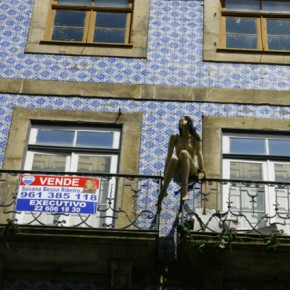 "2010-04-29 Oporto, Portugal a mannequin set up on a balcony with a ""for sale"" sign on an old building"