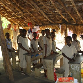 2011-04-08 Togo, Ewe Village School - The classroom is under thatch with no walls and the children wear uniforms of threadbare beige cloth. They had prepared some songs for us and were delighted to have us visit.