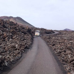 Buses drive through the lava fields of Timanfaya Park, Lanzarote, Canary, Islands